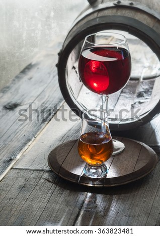 Wineglasses of wine and whiskey and old barrel on a table - stock photo