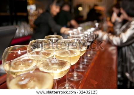 Wineglasses on bar counter with blurred crowd in background - stock photo