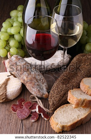 wineglasses with salami, bread and grapes