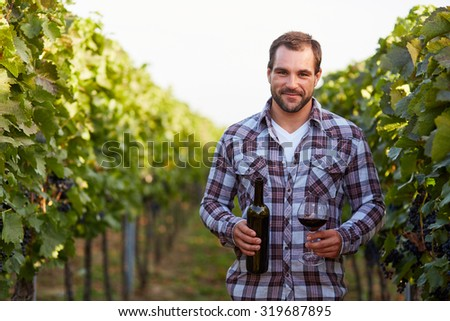 Winemaker in vineyard with a glass of red wine and bottle - stock photo