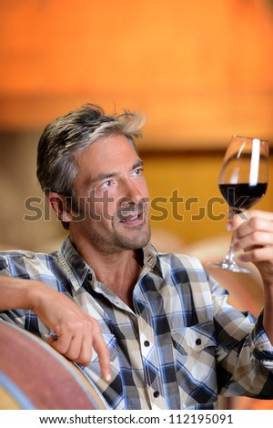 Winemaker looking at red wine in glass - stock photo