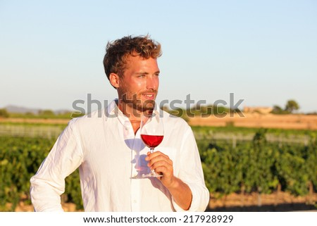 Winemaker man drinking rose or red wine at vineyard from wine glass outdoors. - stock photo