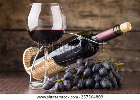 Winery background. Elegant wineglass with bottle of red wine and cluster of grape. - stock photo
