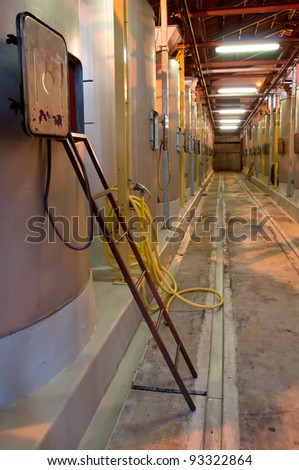 Winery hall with steel wine tanks and ladder - stock photo
