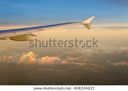 Wing of a Airplane at sunset with Swiss Alps