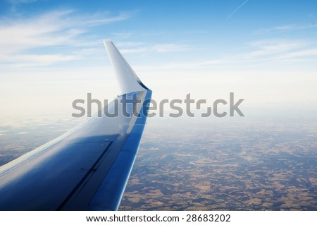 Wing of a passenger airplane at an altitude of 30,000 feet - stock photo