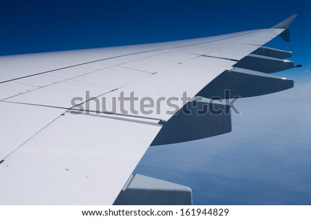 Wing of Airbus A380 in sky - stock photo