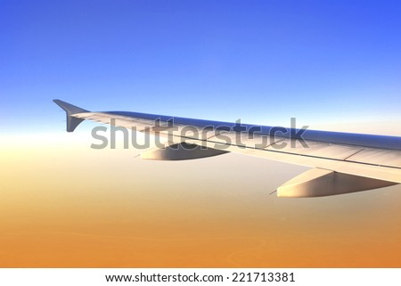 Wing of aircraft in beautiful sunrise light  - stock photo