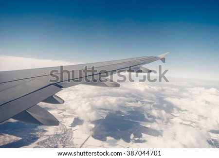 Wing of aircraft seen through window copyspace on cloudscape