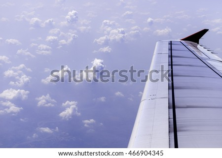 Wing of airplane - flight over white clouds