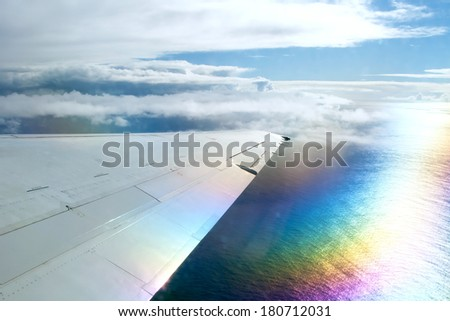 Wing of airplane flying above clouds in the sky and with a view of the ocean in background - stock photo