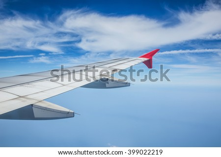 Wing of airplane flying above the clouds in the blue sky.