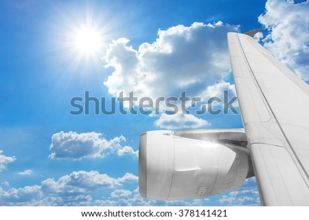 Wing of airplane from window and blue sky - stock photo