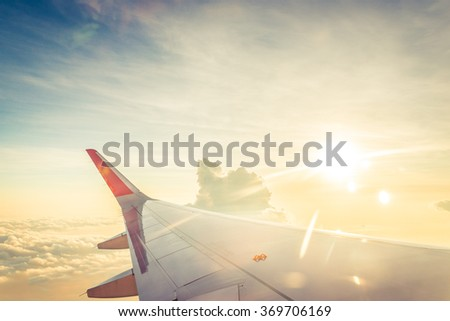 Wing of airplane on cloud sky from window (Vintage Tone) - stock photo