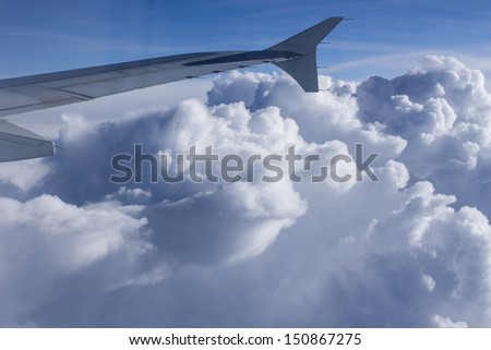 Wing of airplane, view through the window with clouds