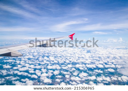 Wing of an airplane flying  - stock photo