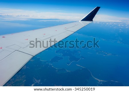 Wing of an airplane flying above a coastal region.  - stock photo