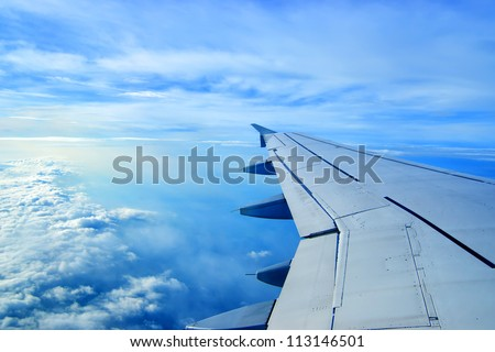 Wing of an airplane flying above the clouds. people looks at the sky from the window of the plane, using airtransport to travel. - stock photo