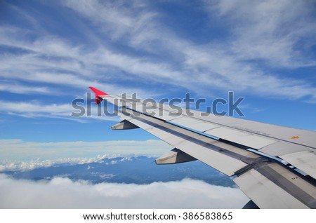 Wing of an airplane flying above the clouds. people looks at the sky from the window of the plane, using air transport to travel or go home