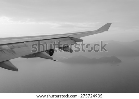 Wing of an airplane flying above the sea near Hong Kong - stock photo