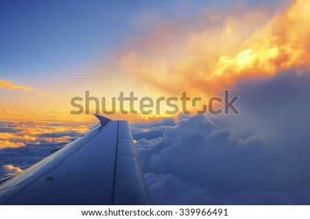 Wing of an airplane flying above the sunset clouds - stock photo
