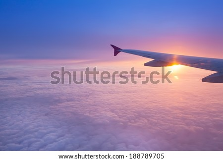 Wing of an airplane in the sunset - stock photo