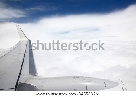Wing of an airplane, view from airplane window with blue sky and white clouds. - stock photo