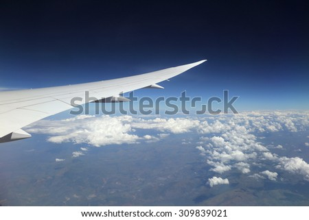 Wing of an airplane with blue sky and while clouds down below.