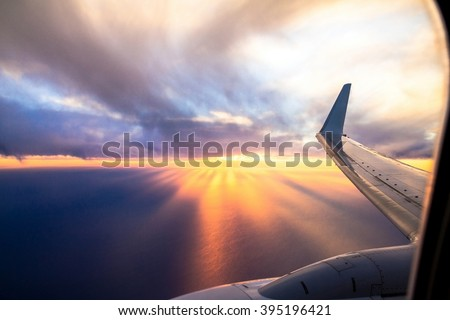 Wing  of big airplane on beautiful orange sunset background, fast aerial transport, traveling and voyage concept. Looking Out Through Airplane Window - stock photo