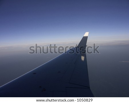 Wing of Plane in Flight with Sun Setting