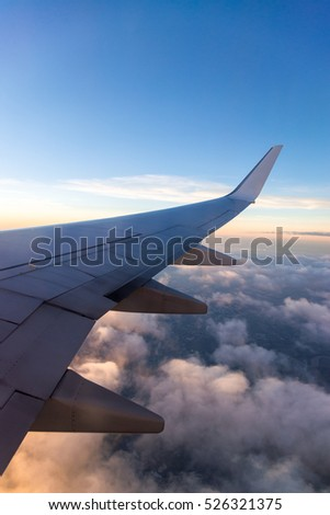 Wing of the air plane on the sea of clouds blue sky background from window airplane