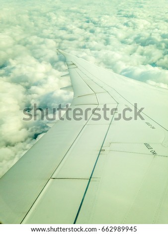 Wing of  the airplane over the white cloud.
