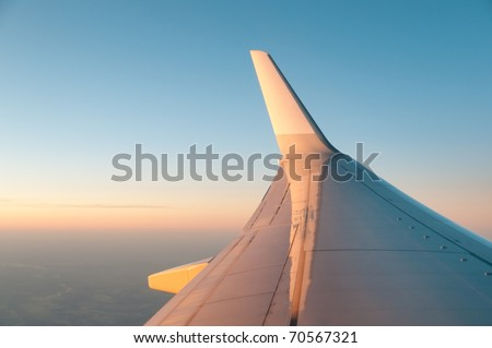 Wing of the plane lit by the sunset on a background of sky - stock photo
