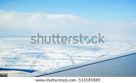 Wing of the plane on blue sky background and snowy  below, view from window of a jet plane wing