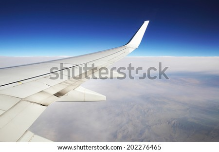 Wing of the plane on sky background - view from the window of a plane of the wing, the sky - View of jet plane wing