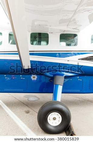 wing, porthole and landing gear light aircraft - stock photo