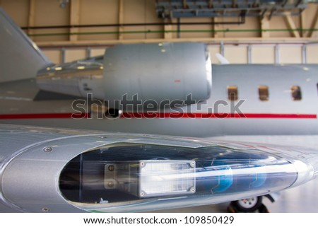wing with lights and engine private plane against  against the hangar - stock photo