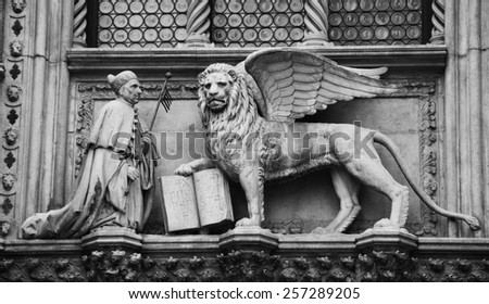 Winged lion holding opened book (inscription in Latin: Pax tibi Marce evangelista meus (May Peace be with you, Mark, my evangelist)) and Doge statues over entry to Doge's Palace in Venice (Italy) - stock photo
