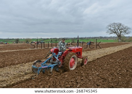 WINGFIELD - APR 4: A tractor pulls a plough through a field on Apr 4, 2015 in Wingfield, UK. Widespread use of tractors emerged during mechanisation of the agricultural industry in the 1950s. - stock photo
