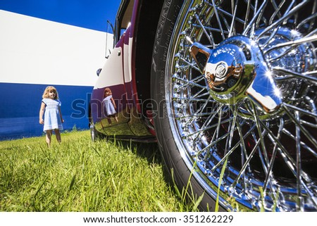 WINGS & WHEELS  CALGARY CANADA 21 6 2015:Father's Day Weekend where some vintage Cars and Aircrafts on display. A Burgundy MG on display with a beautiful young child. - stock photo