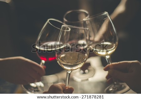 Wining with friends Four friends cheering Drinking wine in a restaurant - stock photo
