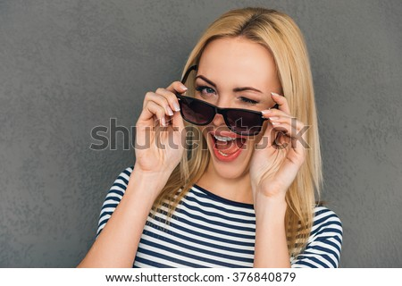 Wink from beauty. Beautiful young woman adjusting her sunglasses and winking while standing against grey background - stock photo