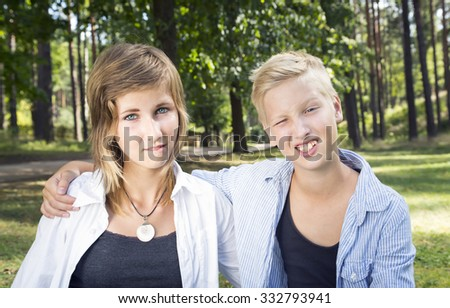 Winking boy and unsure girl sitting on the green grass in nature sunny day. Concept of positive thoughts and emotions. - stock photo