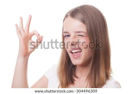 Winking charming girl with OK sign on isolated white - stock photo