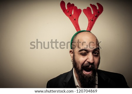 winking christmas bearded man with funny expressions on grey background
