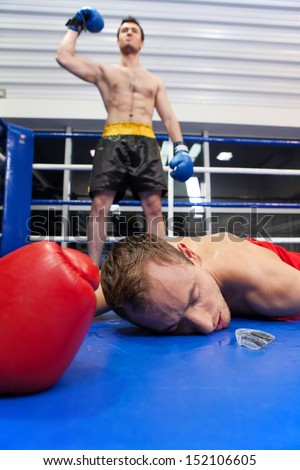 Winner and loser. Confident young boxer keeping his arm raised while his opponent lying down on the boxing ring - stock photo
