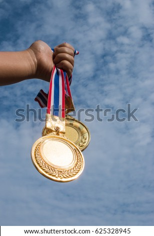winner hand raised and holding two gold medals against blue sky. success award concept