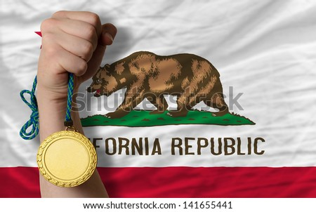 Winner holding gold medal for sport and flag of us state of california - stock photo