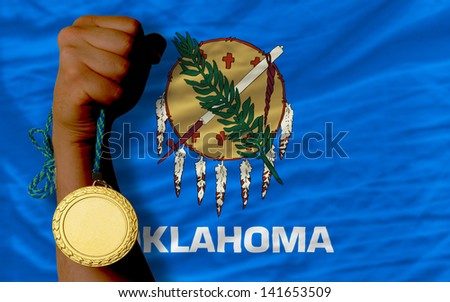 Winner holding gold medal for sport and flag of us state of oklahoma - stock photo
