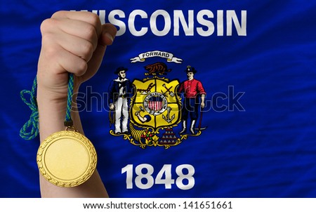 Winner holding gold medal for sport and flag of us state of wisconsin - stock photo